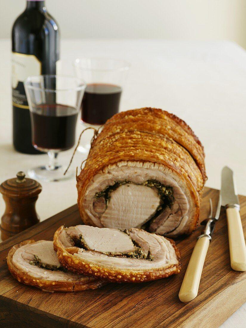 Rolled pork roast with crackling, partly carved
