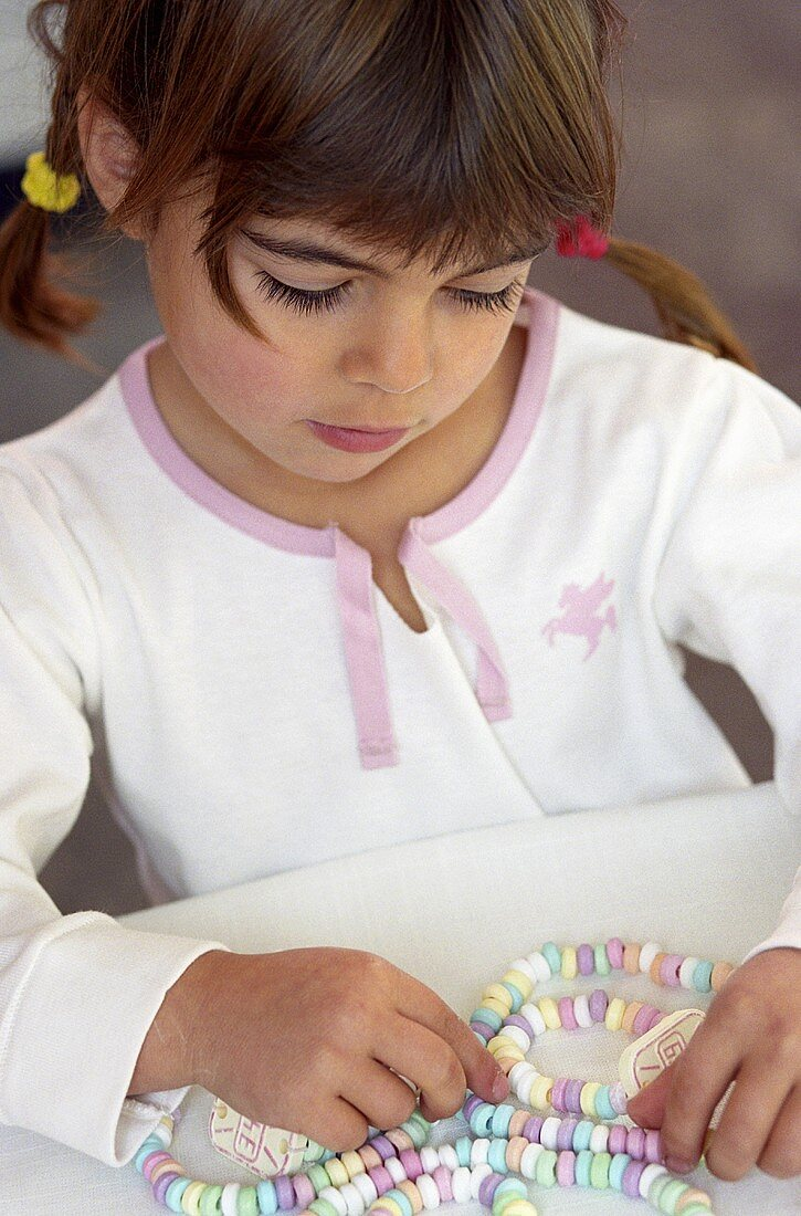 Small girl with candy necklace and candy watches