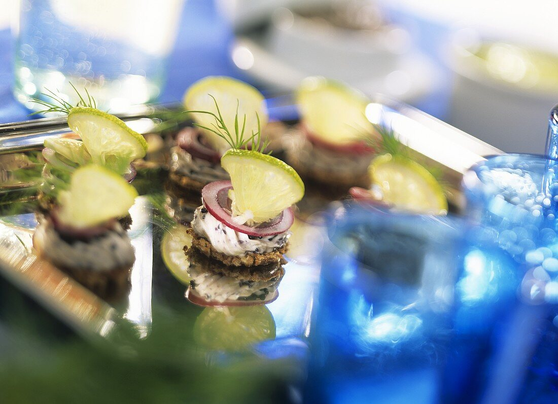 Beluga caviar canapés with onion rings and slices of lime