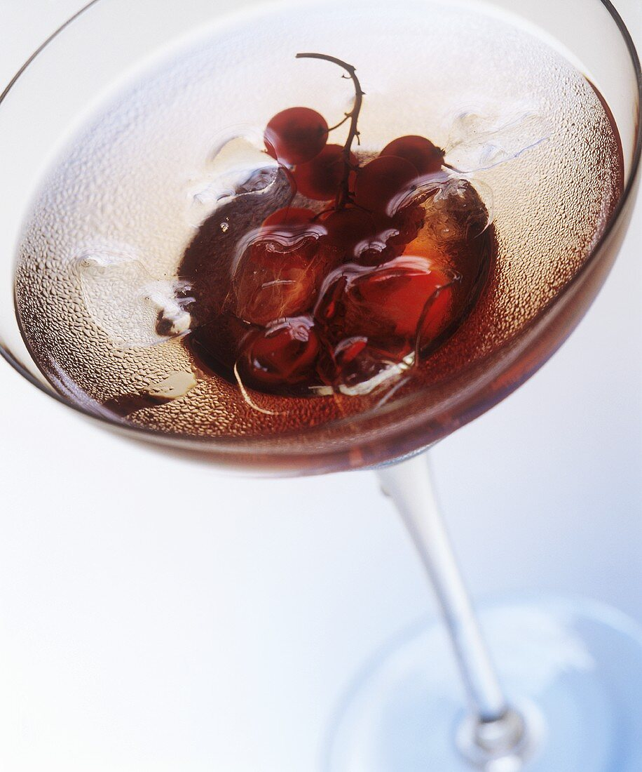 Cassis liqueur cocktail with redcurrants and ice cubes