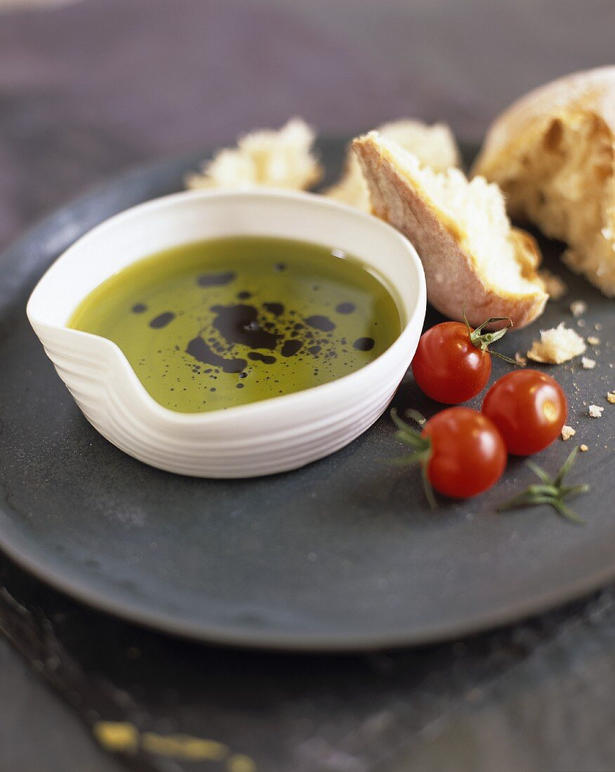 A dish of olive oil, cherry tomatoes and ciabatta