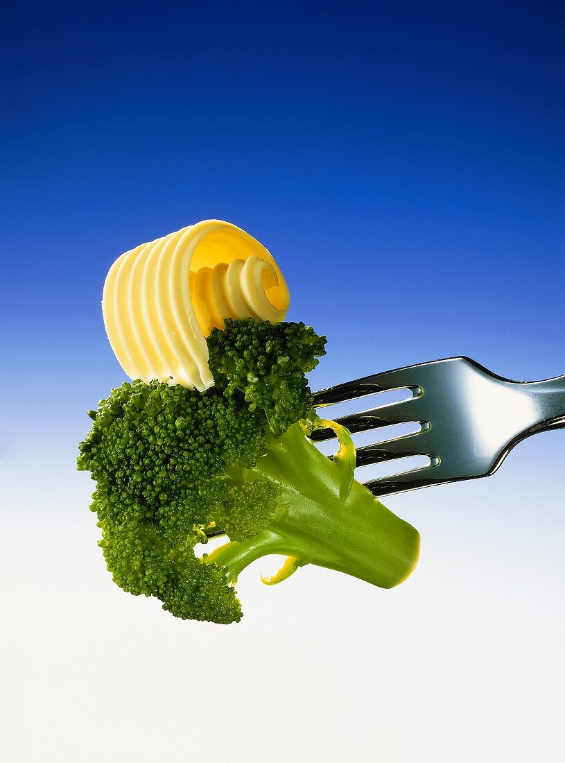 A broccoli floret with butter curl, on a fork