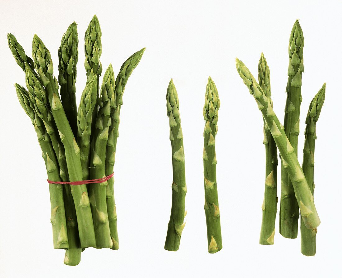 Several spears of green asparagus on white background