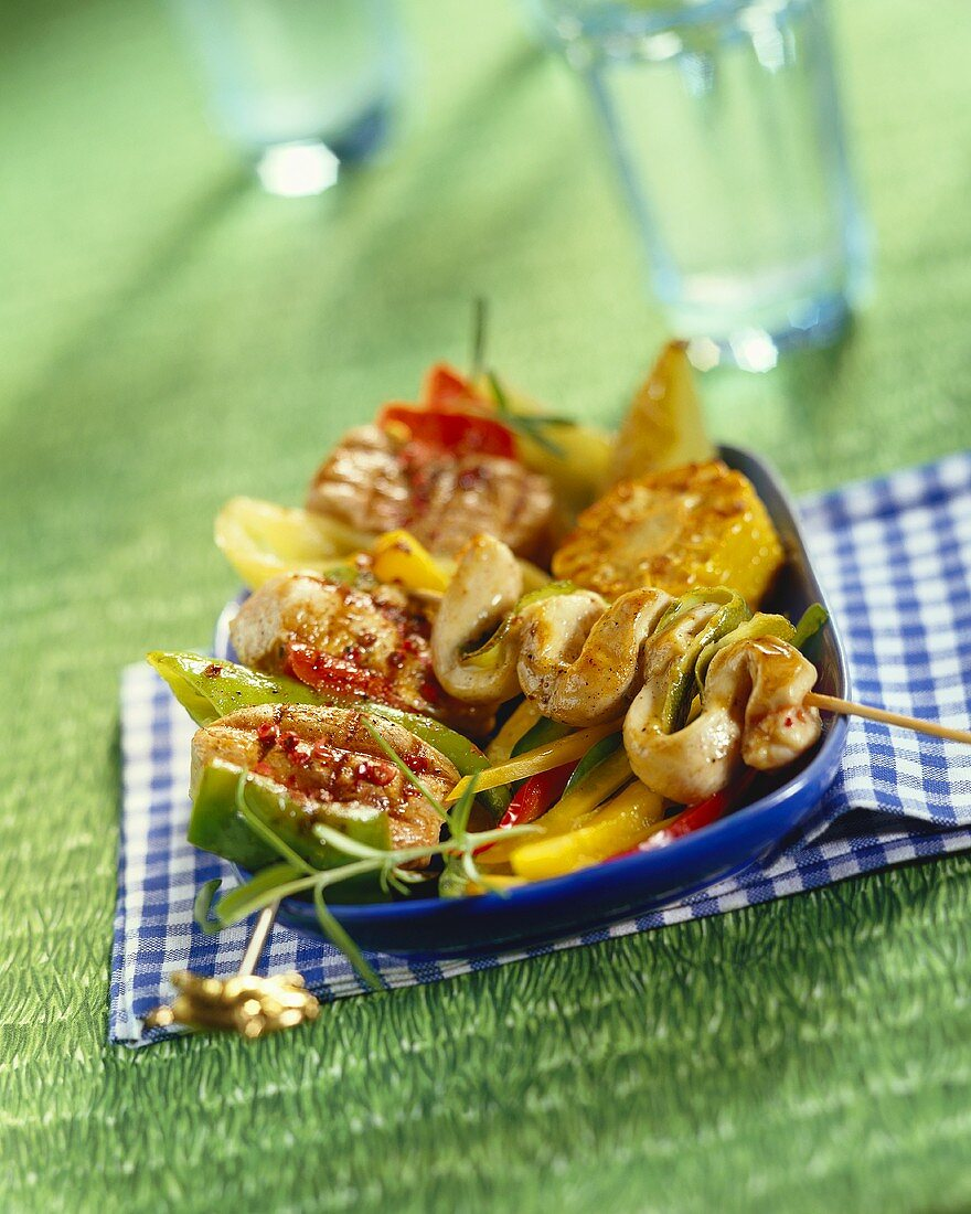 Barbecued chicken kebabs on a bed of vegetables
