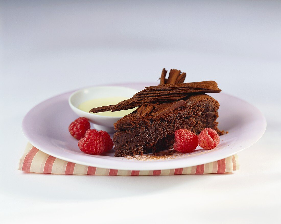 A piece of chocolate cake with raspberries and custard