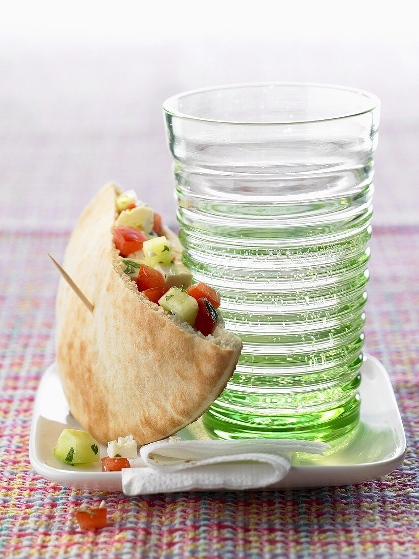 Pita bread filled with vegetables leaning against a glass