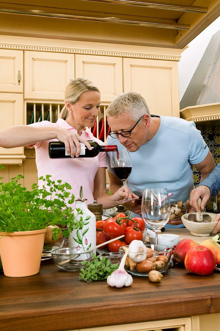 Couple tasting red wine whilst cooking