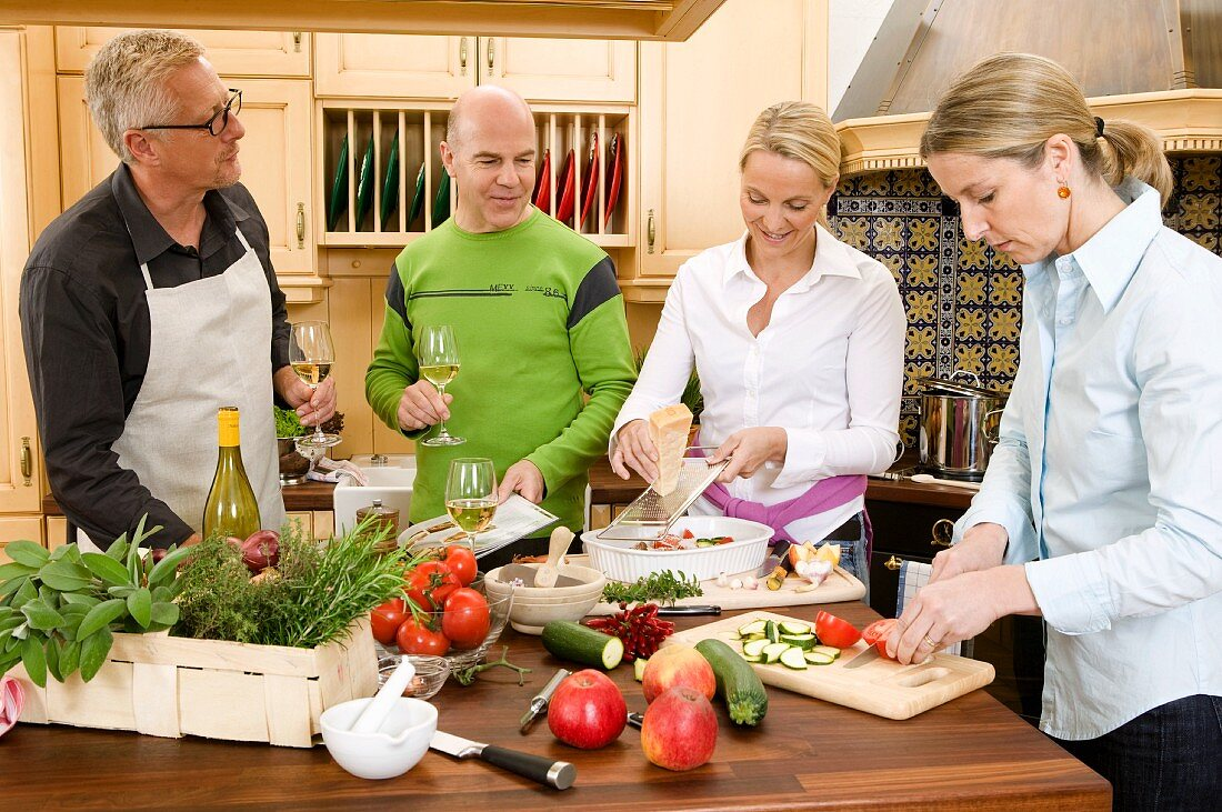 Two couples preparing evening meal together