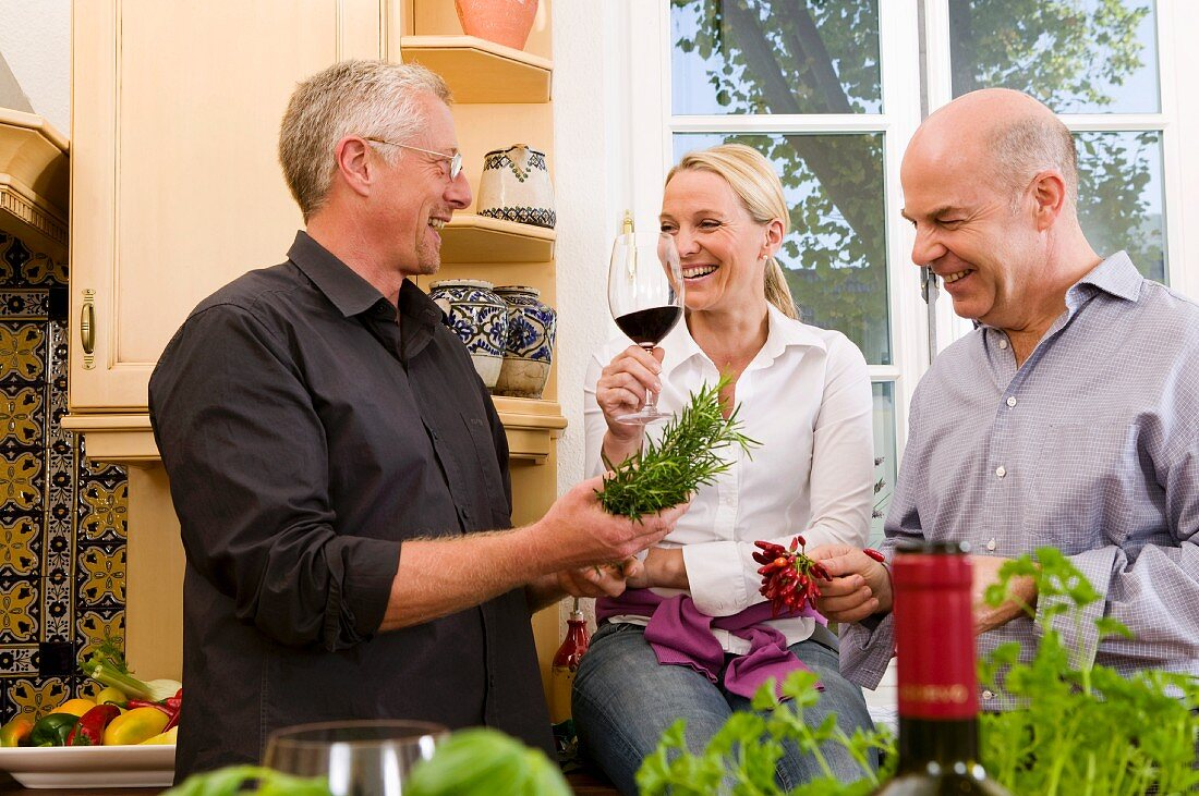 Friends in kitchen with herbs, red wine and chillies