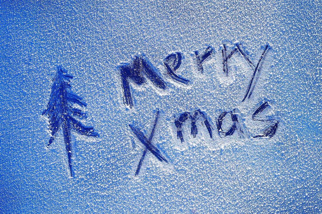 Merry Xmas written on sheet of ice