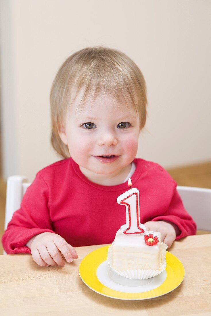 Small girl with a first birthday cake