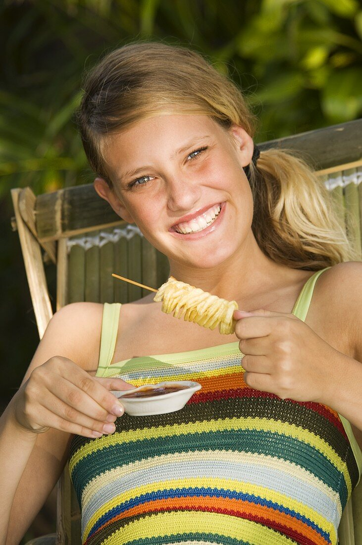 Young woman in deckchair eating potato crisps