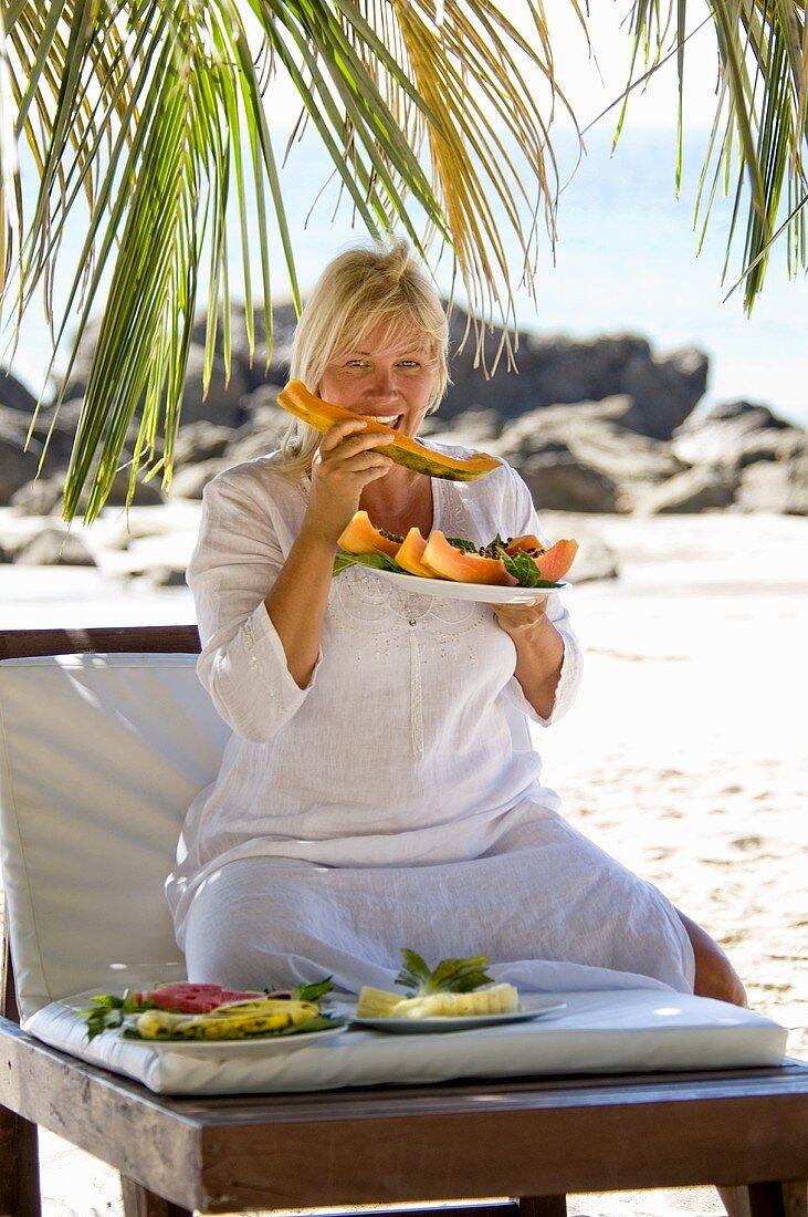 Blond woman eating papaya on the beach