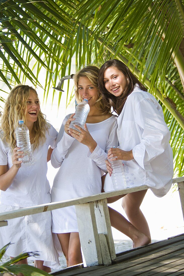 Three girls with bottles of water under palm trees