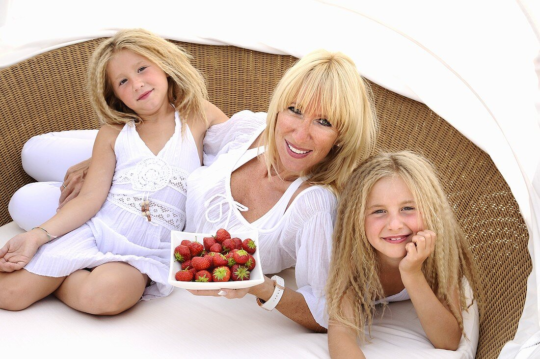 Mother and daughters with strawberries