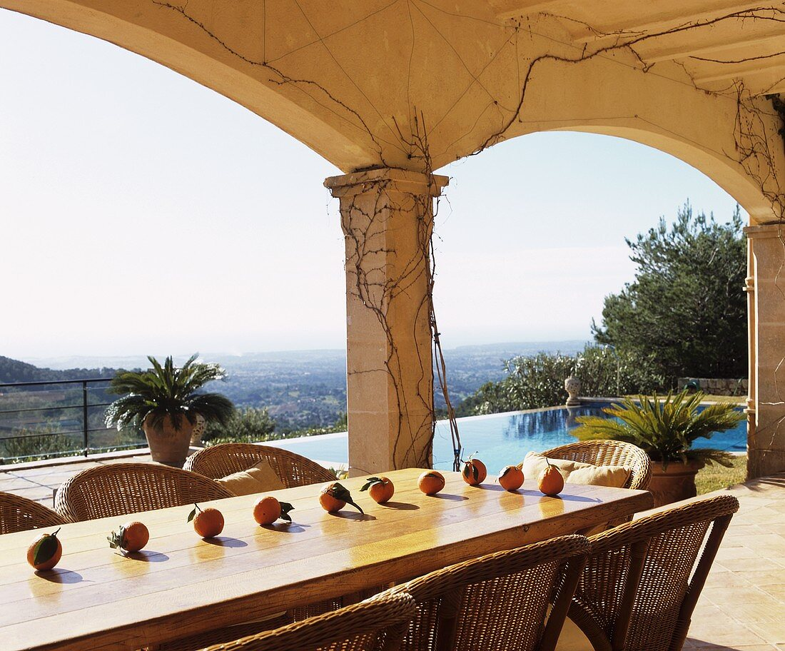 Dining table with mandarin oranges on roofed terrace