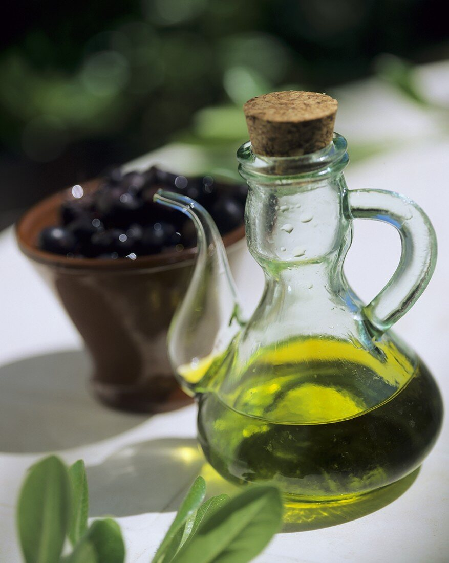 Olive oil in a glass jug and a small dish of olives