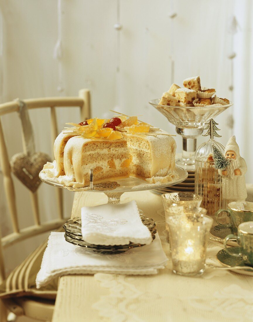 Orange marzipan cake and stollen squares on festive table