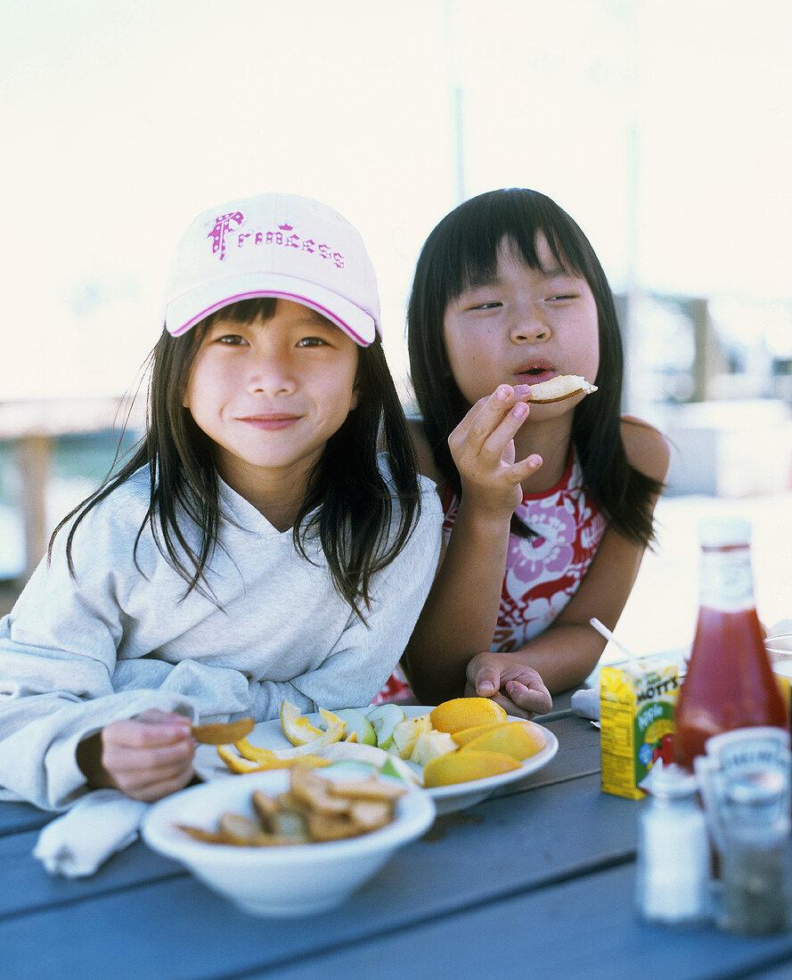 Two girls eating fruit wedges