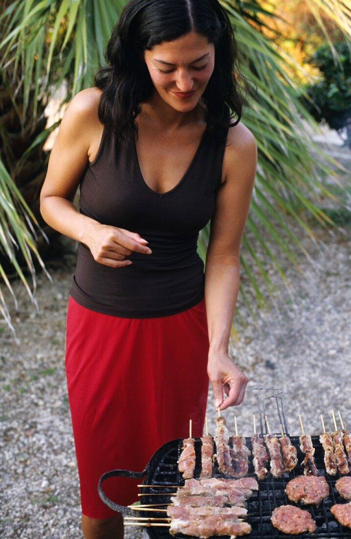 Young woman barbecuing under palm trees