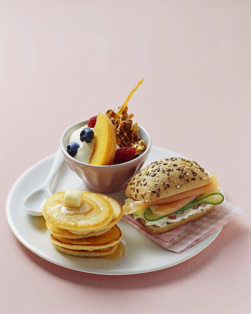 Breakfast plate: pancakes, sandwich roll, muesli with yoghurt