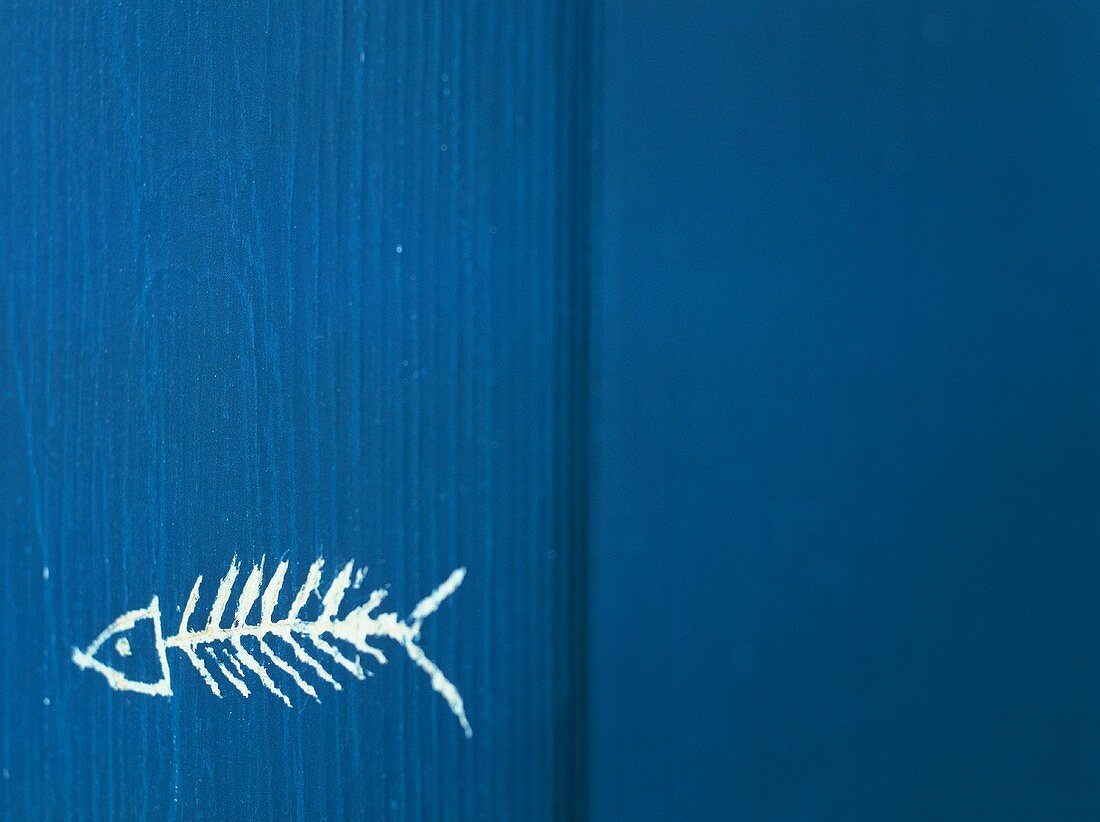 Fishbone painted on blue wooden background