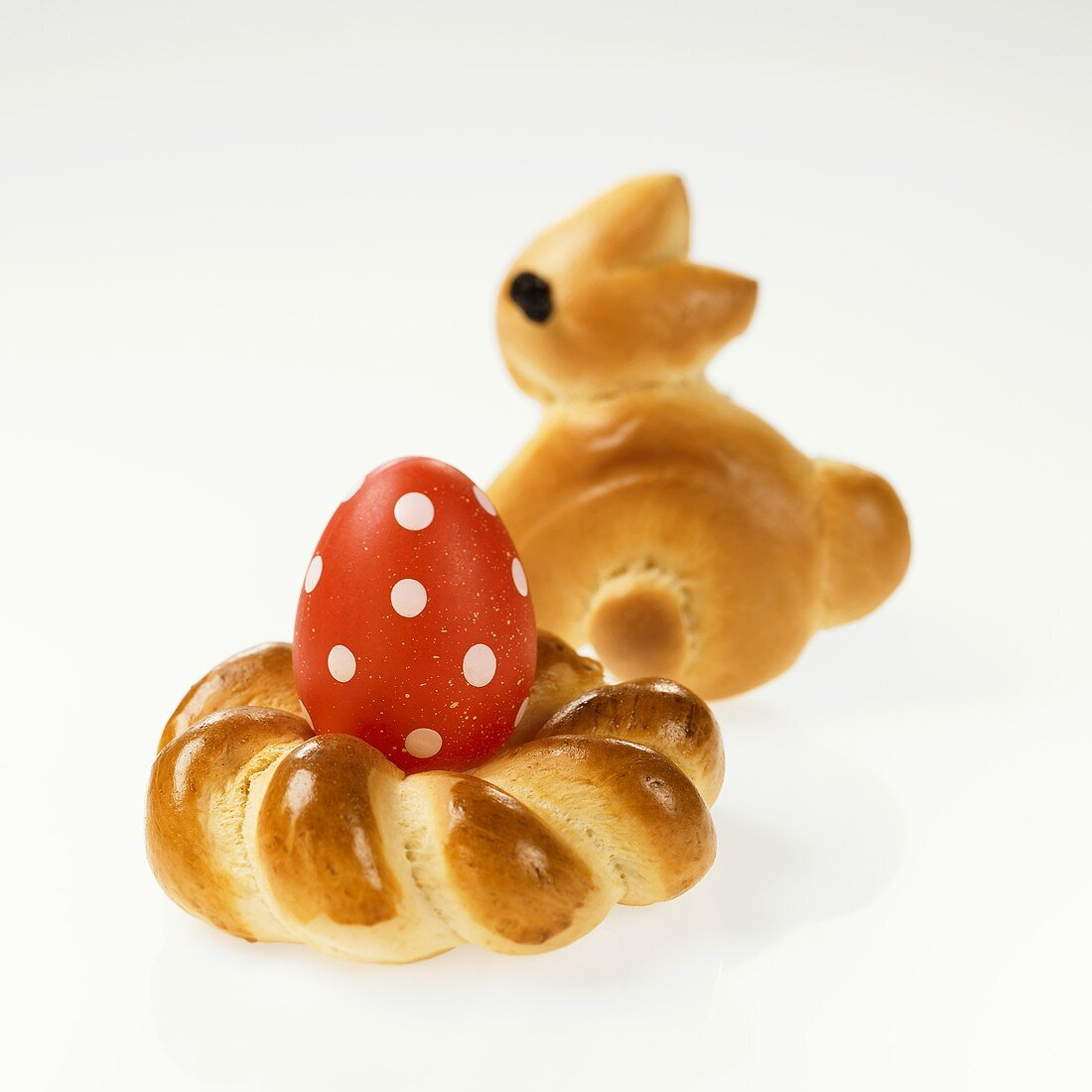 Coloured egg in baked Easter nest with baked Easter Bunny