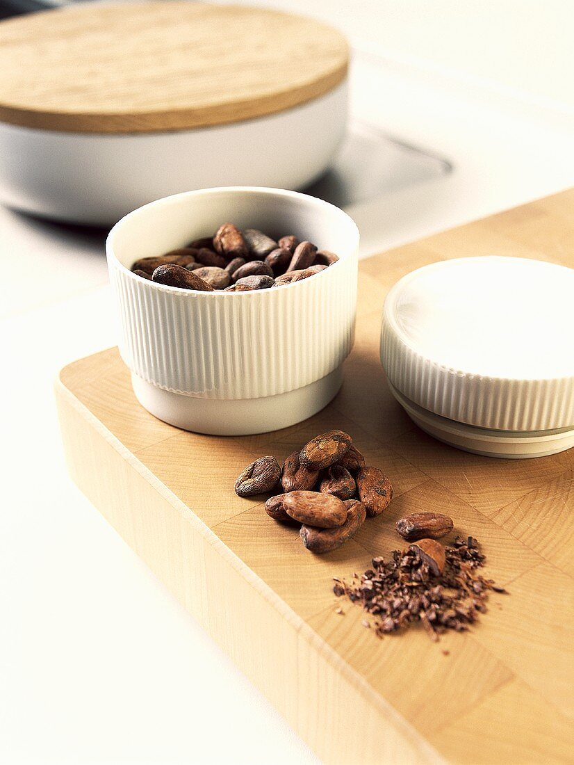 Cocoa beans, whole and crushed on board and in small dish