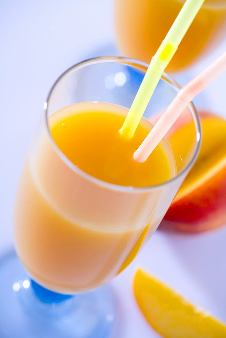 A glass of peach nectar with straws