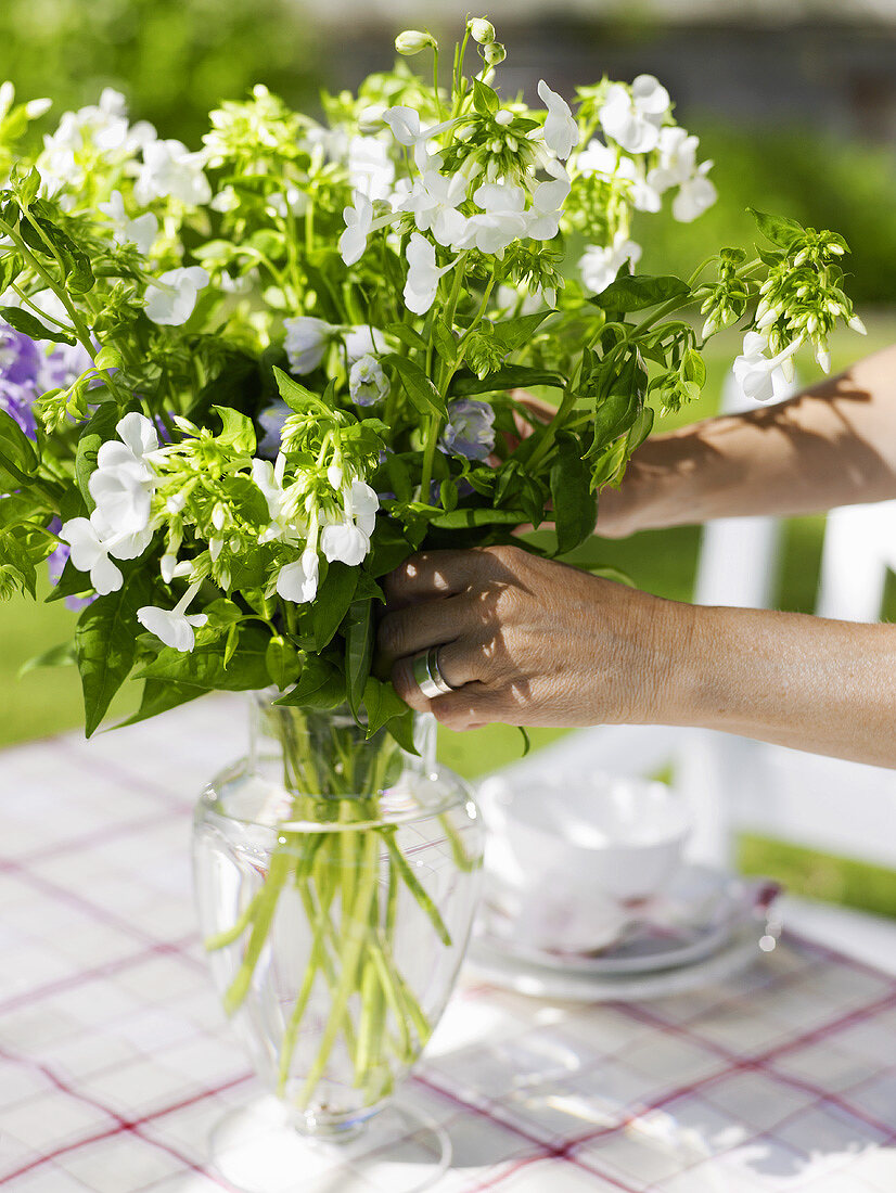 Arranging flowers on table laid for coffee in garden