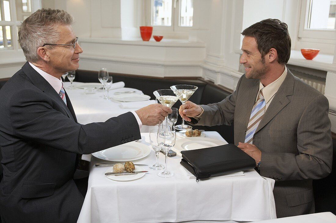 Two men clinking glasses of Martini in a restaurant