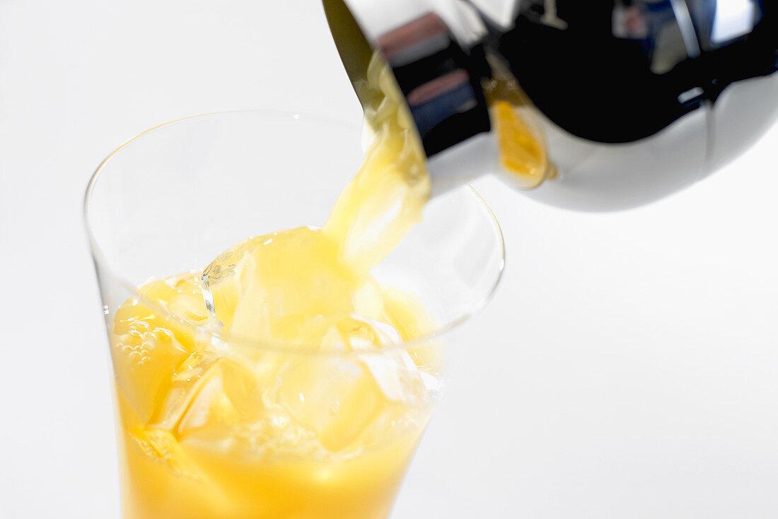 Pouring fruit cocktail out of cocktail shaker into glass