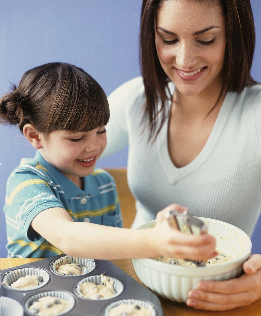 Mother and daughter baking muffins together