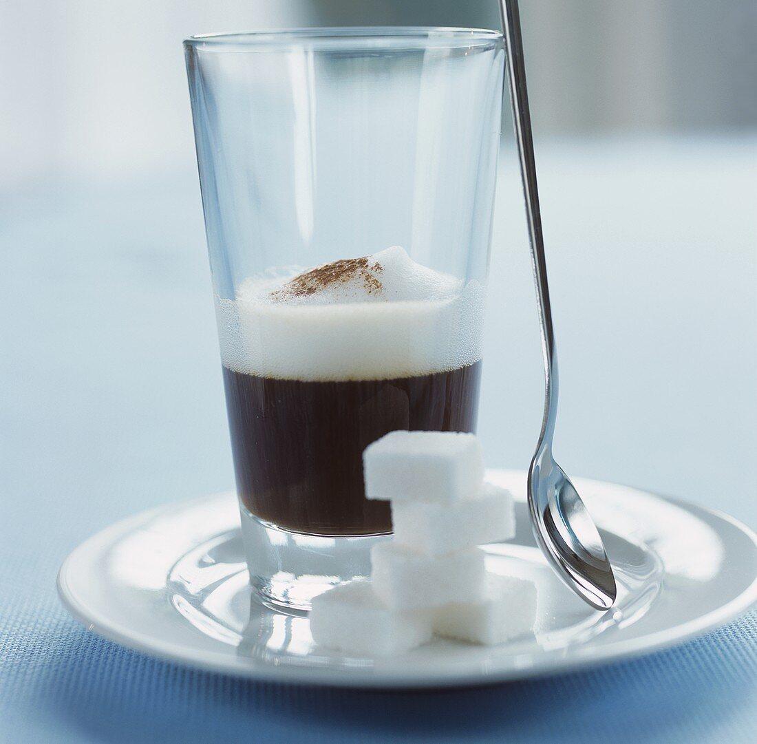 A glass of espresso macchiato, sugar