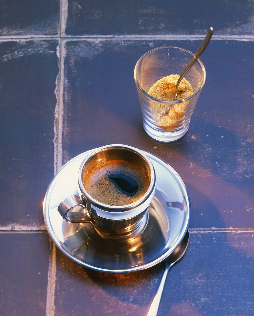 Espresso in silver cup and saucer with brown sugar on tiles