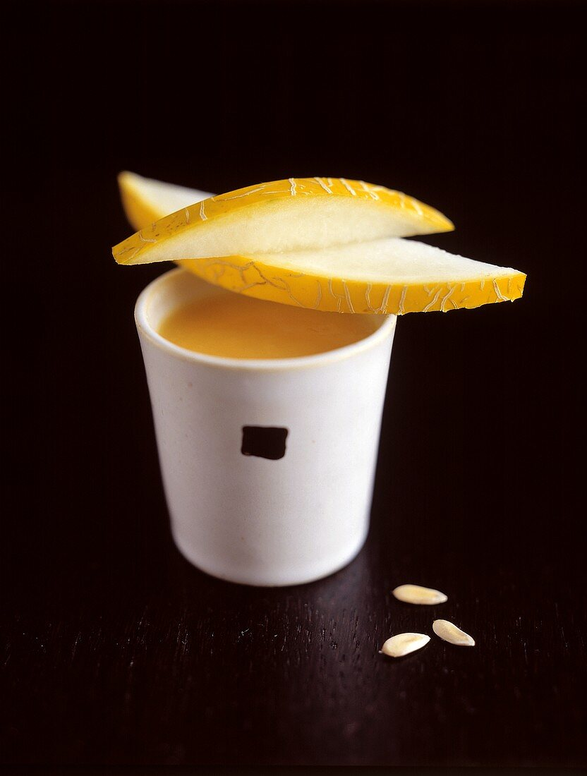 A Cup of Pumpkin Soup with Melon Slices and Seeds