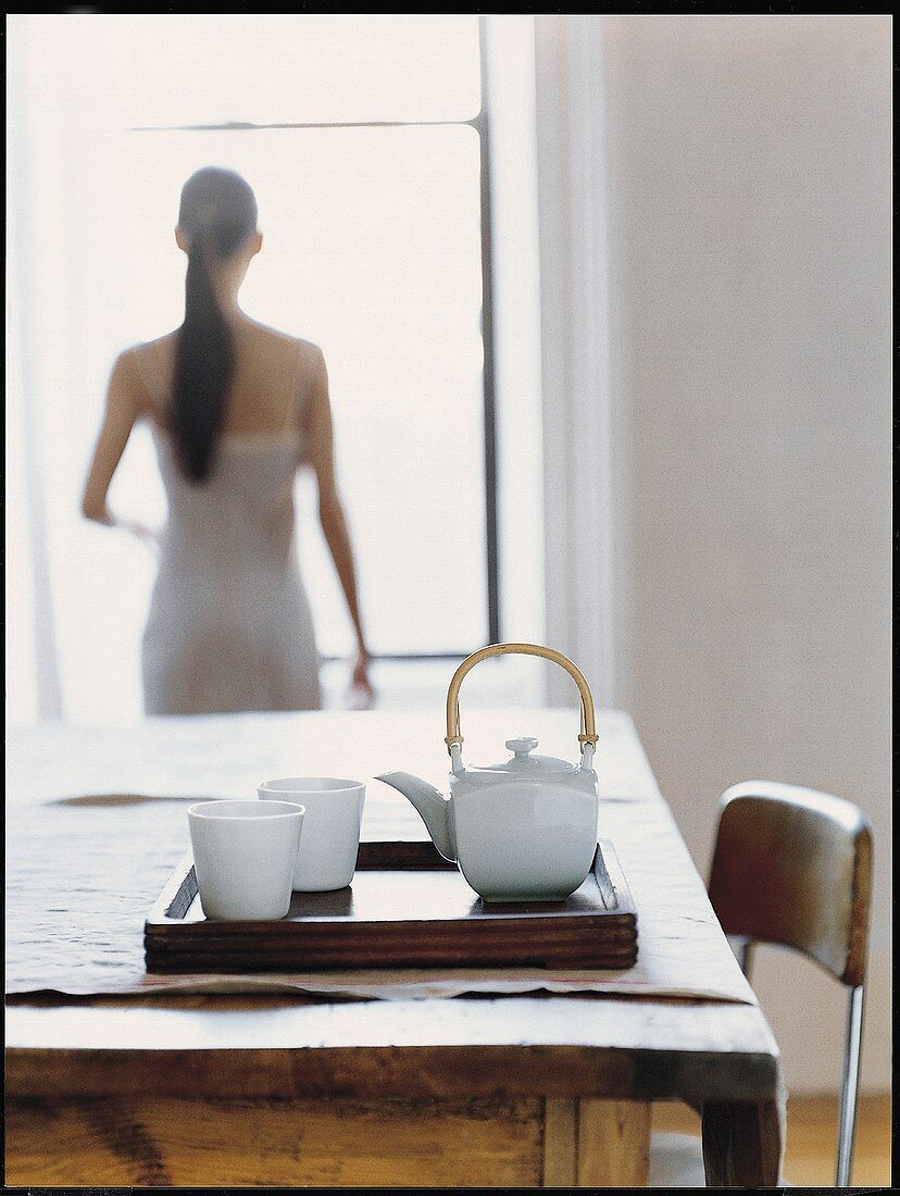 Tray with tea things on wooden table; woman in background
