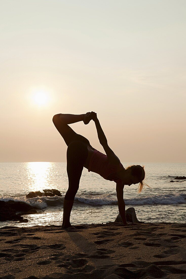 A woman practicing yoga on a beach at sunset
