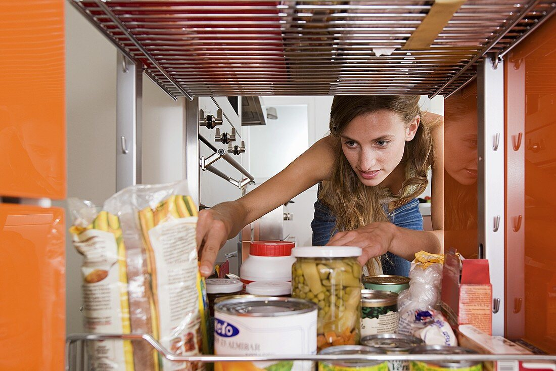A woman reaching for a packet of food