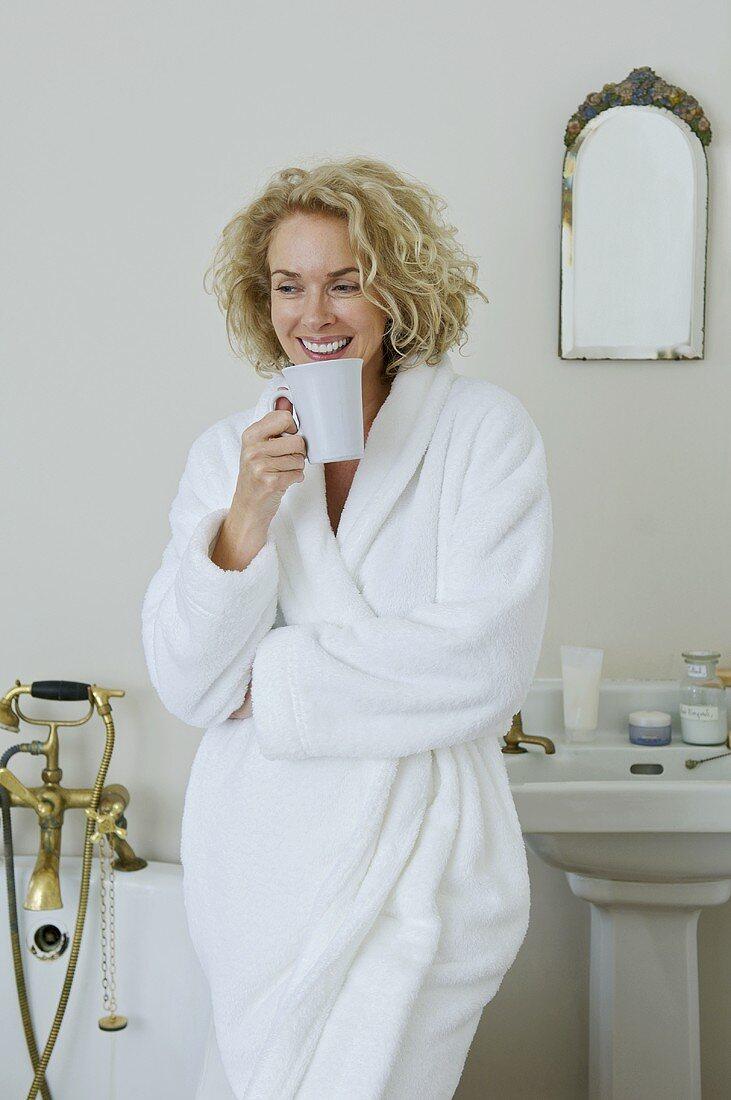 A woman drinking coffee in a bathroom
