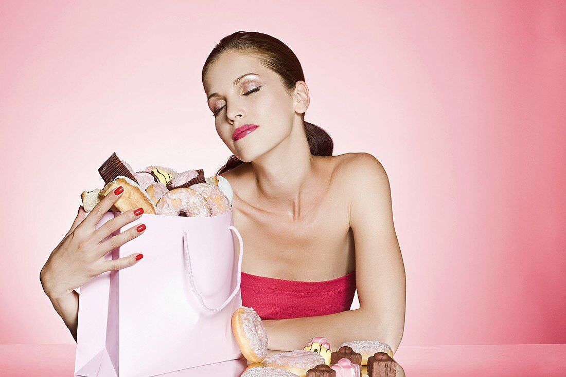 A young woman with a bag of cakes and doughnuts