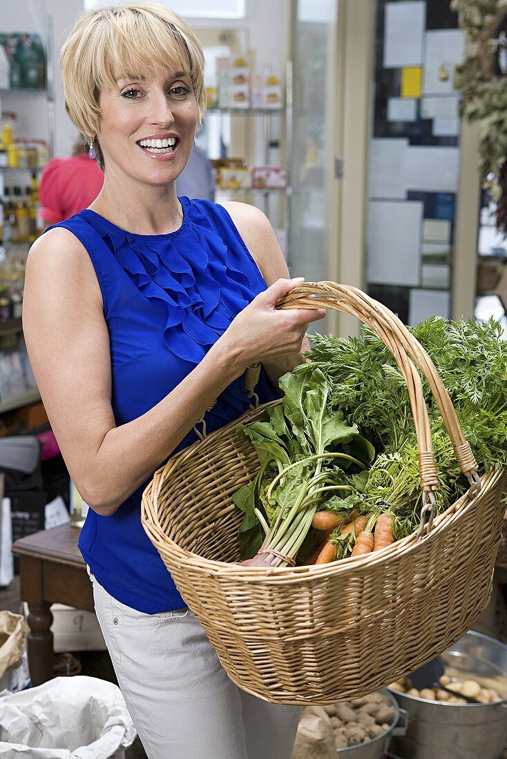 A woman in a store with a basket of vegetables