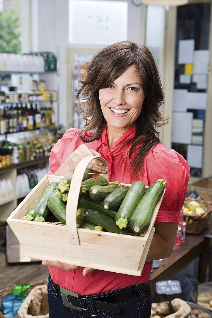 Woman in store with courgettes