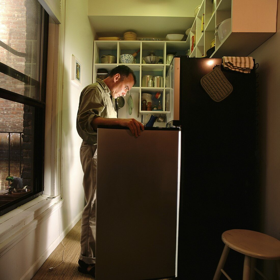 A man looking in a refrigerator