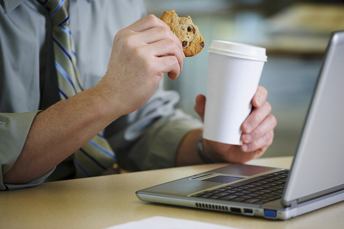 A man at a desk with coffee and a cookie
