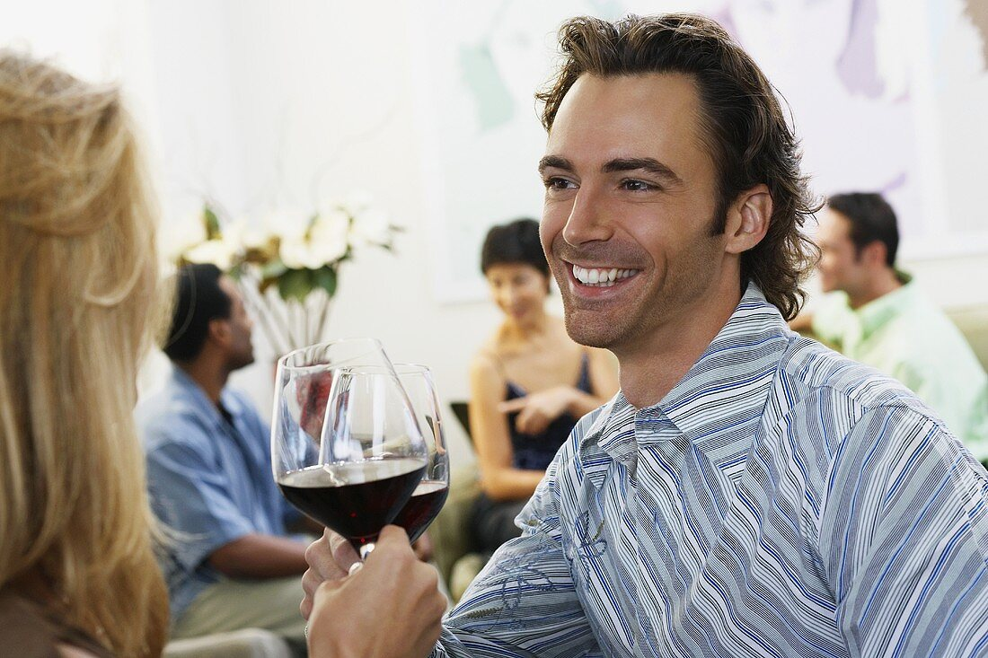 A couple at a party with glasses of red wine