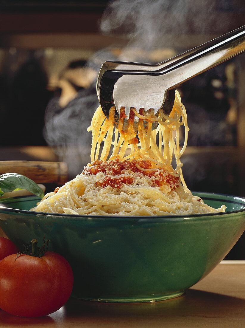 Bowl of Spaghetti with Tomato Sauce; Tongs