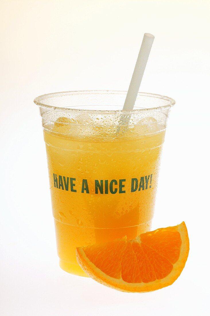 Orange juice in plastic tumbler with straw; orange wedge