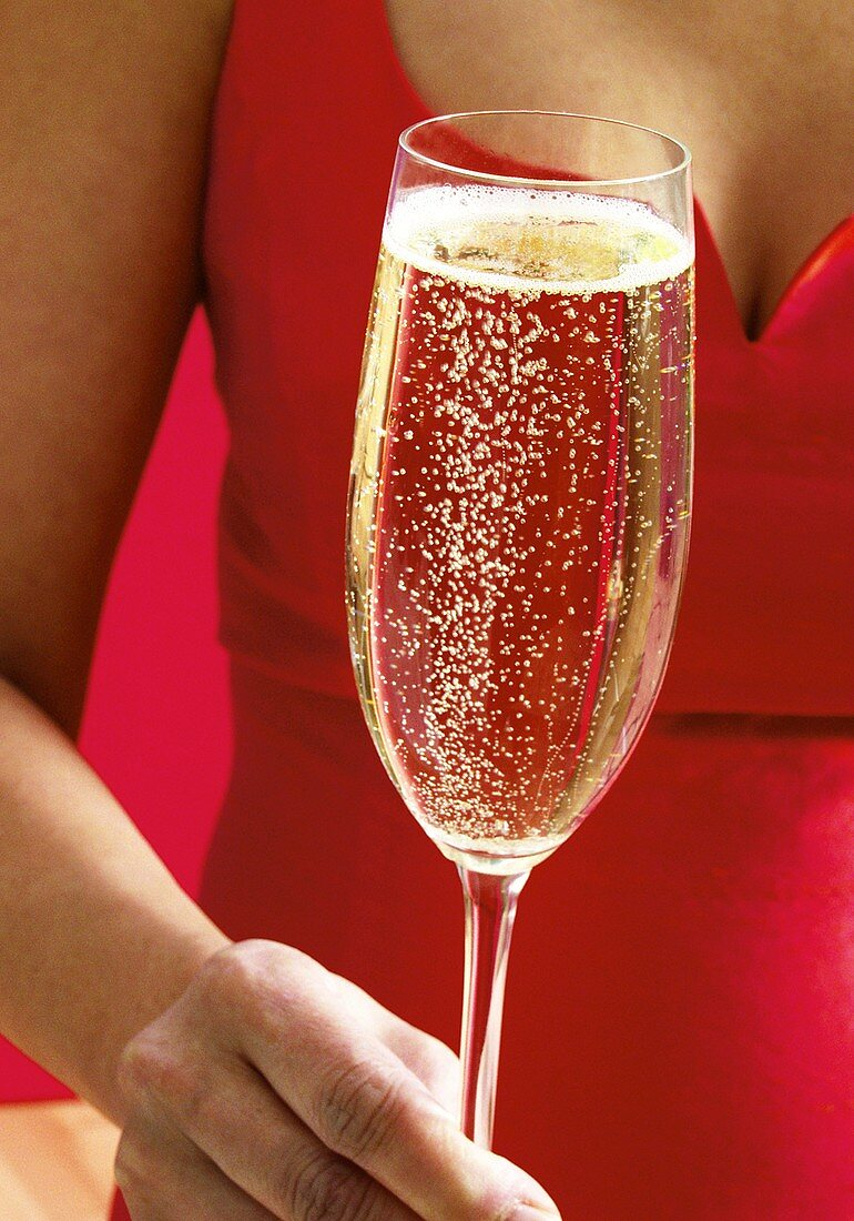 Woman in red dress holding champagne glass