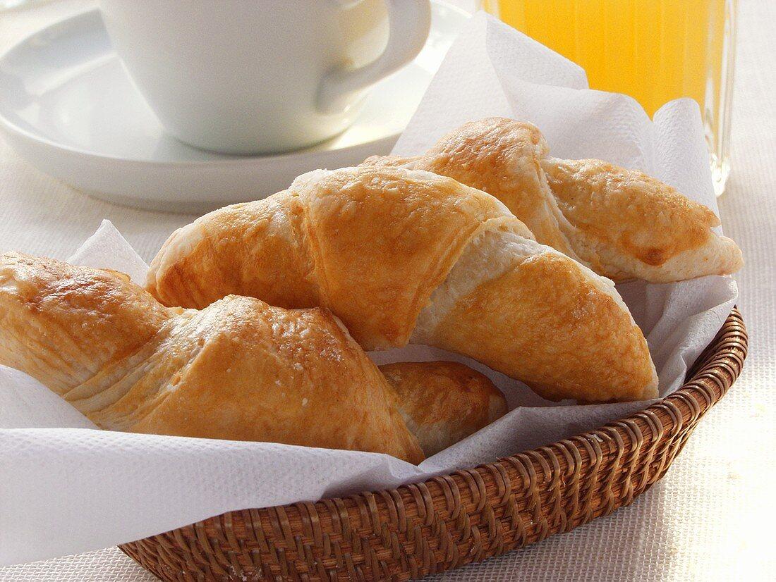 Croissants in bread basket, grapefruit juice & coffee cup